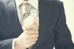 Κλείστε επάνω μιας επιχείρησης επανδρώνει τα κρύβοντας χρήματα χεριών στην τσέπη σακακιών κοστουμιών του Στοκ Εικόνες