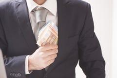 Κλείστε επάνω μιας επιχείρησης επανδρώνει τα κρύβοντας χρήματα χεριών στην τσέπη σακακιών κοστουμιών του Στοκ εικόνες με δικαίωμα ελεύθερης χρήσης