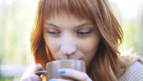 Κλείστε επάνω μιας κοκκινομάλλους γυναίκας που πίνει ένα καυτό ποτό σε ένα πάρκο απόθεμα βίντεο