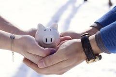 Κλείστε επάνω μιας μικρής piggy τράπεζας εκμετάλλευσης ζευγών στα χέρια Στοκ Φωτογραφία