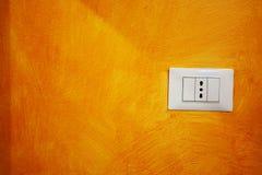 Κλείστε επάνω μιας υποδοχής σε έναν πορτοκαλή τοίχο στοκ εικόνες