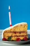 Κλείστε επάνω μιας φέτας του κέικ γενεθλίων με το κερί Στοκ Εικόνες