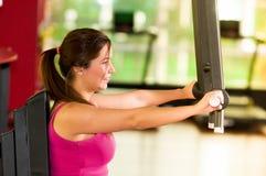 Κλείστε επάνω μιας όμορφης γυναίκας που κάνει τις θωρακικές ασκήσεις στη γυμναστική Στοκ Εικόνα