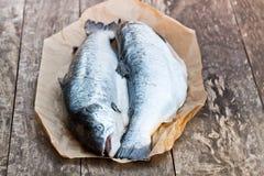 Κλείστε επάνω ολόκληρα τα ακατέργαστα salmons ξύλινο υπόβαθρο Στοκ φωτογραφία με δικαίωμα ελεύθερης χρήσης