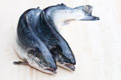 Κλείστε επάνω ολόκληρα τα ακατέργαστα salmons στο ξύλινο υπόβαθρο Στοκ εικόνα με δικαίωμα ελεύθερης χρήσης