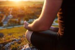 Κλείστε επάνω σε ετοιμότητα αρσενικά που στη θέση γιόγκας ενάντια στο όμορφο ηλιοβασίλεμα Στοκ Εικόνες