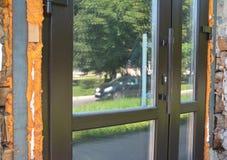 Κλείστε επάνω στην εγκατάσταση και τη μόνωση πορτών γυαλιού με τον αφρό στοκ φωτογραφία