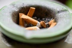 Κλείστε επάνω στον επιβαρυνμένο δίσκο τέφρας με τα μμένα τσιγάρα Στοκ Εικόνες