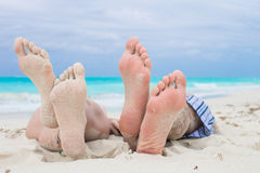 Κλείστε επάνω τα αρσενικά και θηλυκά πόδια στην άσπρη άμμο στοκ εικόνες