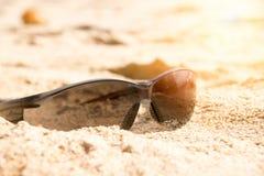 Κλείστε επάνω τα γυαλιά ηλίου στην αμμώδη παραλία και το φως του ήλιου Στοκ εικόνα με δικαίωμα ελεύθερης χρήσης