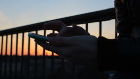 Κλείστε επάνω τα θηλυκά χέρια χρησιμοποιώντας το κινητό τηλέφωνο στο πεζούλι μπαλκονιών στο ηλιοβασίλεμα φωτός του ήλιου απόθεμα βίντεο