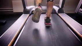 Κλείστε επάνω τα πόδια γυναικών στα πάνινα παπούτσια treadmill στη γυμναστική απόθεμα βίντεο