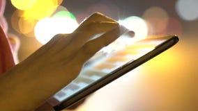 Κλείστε επάνω τα χέρια, δάχτυλα σχετικά με την οθόνη της ταμπλέτας σε μια φωτεινή νύχτα απόθεμα βίντεο