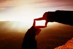 Κλείστε επάνω τα χέρια κάνοντας τη χειρονομία πλαισίων Πορτοκαλής misty φυσητήρας κοιλάδων Ηλιόλουστη χαραυγή άνοιξη στα βουνά Στοκ εικόνες με δικαίωμα ελεύθερης χρήσης