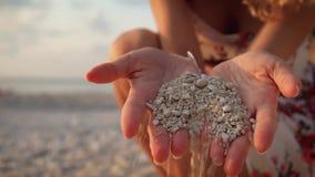 Κλείστε επάνω τα χέρια μιας ψιλοβρέχοντας άμμου θάλασσας γυναικών μέσω των δάχτυλών της φιλμ μικρού μήκους
