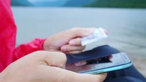 Κλείστε επάνω τα χέρια που κρατούν την πιστωτική κάρτα και που χρησιμοποιούν το κινητό έξυπνο τηλέφωνο υπαίθριο απόθεμα βίντεο