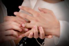 Κλείστε επάνω τα χέρια της νύφης και ο νεόνυμφος που βάζει σε έναν γάμο χτυπά Στοκ Φωτογραφίες