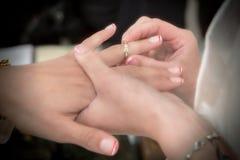 Κλείστε επάνω τα χέρια της νύφης και ο νεόνυμφος που βάζει σε έναν γάμο χτυπά Στοκ Φωτογραφία
