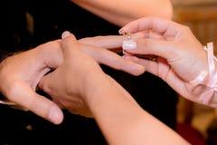 Κλείστε επάνω τα χέρια της νύφης και ο νεόνυμφος που βάζει σε έναν γάμο χτυπά Στοκ Εικόνα