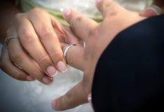 Κλείστε επάνω τα χέρια της νύφης και ο νεόνυμφος που βάζει σε έναν γάμο χτυπά Στοκ φωτογραφία με δικαίωμα ελεύθερης χρήσης