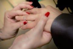 Κλείστε επάνω τα χέρια της νύφης και ο νεόνυμφος που βάζει σε έναν γάμο χτυπά Στοκ φωτογραφίες με δικαίωμα ελεύθερης χρήσης