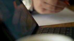 Κλείστε επάνω τα χέρια των λειτουργώντας σημειώσεων γραψίματος ατόμων καθμένος στον πίνακα στον καφέ φιλμ μικρού μήκους