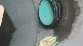 Κλείστε επάνω τεθειμένο το εργαζόμενος τσιμέντο γύρω από το μαύρο και πράσινο σωλήνα στο σκυρόδεμα απόθεμα βίντεο
