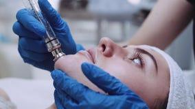 Κλείστε επάνω την άποψη ενός νέου θηλυκού ασθενή που έχει ένα επαγγελματικό του προσώπου κενό μασάζ Θεραπευτικές διαδικασίες, παρ φιλμ μικρού μήκους