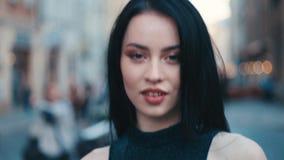 Κλείστε επάνω την άποψη μιας όμορφης νέας γυναίκας που περπατά κάτω από την οδό πόλεων, τις στροφές στη κάμερα και τα χαμόγελα se φιλμ μικρού μήκους
