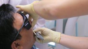 Κλείστε επάνω την άποψη σχετικά με τον οδοντίατρο που λευκαίνει τα δόντια φιλμ μικρού μήκους