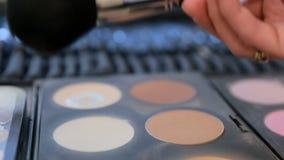 Κλείστε επάνω την άποψη της βούρτσας makeup που κινείται πέρα από την παλέτα χρώματος δερμάτων και σκιάς ματιών φιλμ μικρού μήκους