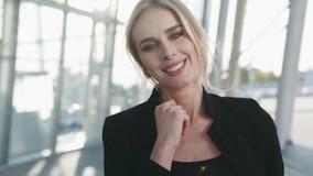 Κλείστε επάνω την άποψη της ελκυστικής νέας μπλε-eyed γυναίκας σε μια κομψή εξάρτηση, χαμογελώντας υπέροχα προς τη κάμερα _ απόθεμα βίντεο