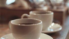 Κλείστε επάνω την άποψη του καυτού καφέ στα τέλεια καθαρά, άσπρα φλυτζάνια στο δρύινο μετρητή Δραστηριότητες καφέδων Όργανα Baris απόθεμα βίντεο