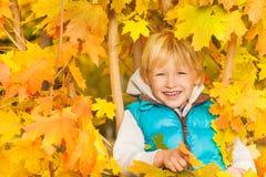 Κλείστε επάνω την άποψη του ξανθού αγοριού στα κίτρινα φύλλα φθινοπώρου Στοκ εικόνα με δικαίωμα ελεύθερης χρήσης