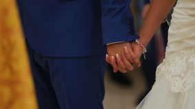 Κλείστε επάνω την άποψη των χεριών εκμετάλλευσης ζευγών που έχουν τη γαμήλια τελετή στην εκκλησία φιλμ μικρού μήκους