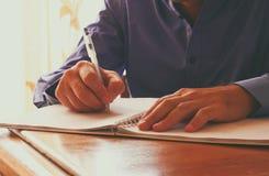 Κλείστε επάνω την εικόνα των αρσενικών χεριών γράφοντας στο σημειωματάριο Εκλεκτική εστίαση Στοκ εικόνα με δικαίωμα ελεύθερης χρήσης