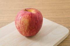 Κλείστε επάνω την κόκκινη Apple σε έναν ξύλινο τέμνοντα πίνακα Στοκ φωτογραφία με δικαίωμα ελεύθερης χρήσης