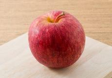 Κλείστε επάνω την κόκκινη Apple στον ξύλινο τέμνοντα πίνακα Στοκ Φωτογραφία