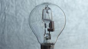 Κλείστε επάνω της λάμπας φωτός πέρα από το ασημένιο υπόβαθρο electricity απόθεμα βίντεο