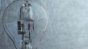 Κλείστε επάνω της λάμπας φωτός πέρα από το ασημένιο υπόβαθρο electricity φιλμ μικρού μήκους