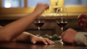 Κλείστε επάνω της αγάπης των χεριών εκμετάλλευσης ζευγών και τα ποτήρια του κόκκινου κρασιού κατά τη διάρκεια του ρομαντικού γεύμ απόθεμα βίντεο