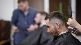 Κλείστε επάνω της γενειοφόρου συνεδρίασης ατόμων με το μαύρο τέμνον ακρωτήριο στο barbershop Ο θηλυκός κουρέας κάνει την τέλεια μ απόθεμα βίντεο