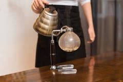 Κλείστε επάνω της γυναίκας με τον κατασκευαστή καφέ σιφωνίων και το δοχείο Στοκ Φωτογραφίες
