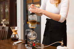 Κλείστε επάνω της γυναίκας με τον κατασκευαστή καφέ σιφωνίων και το δοχείο Στοκ εικόνες με δικαίωμα ελεύθερης χρήσης