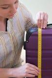 Κλείστε επάνω της γυναίκας που μετρά τη βαλίτσα πριν από τις διακοπές Στοκ Εικόνα