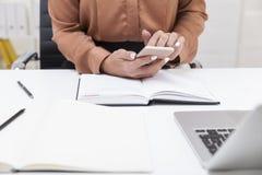 Κλείστε επάνω της γυναίκας στην καφετιά μπλούζα με ένα smartphone Στοκ φωτογραφία με δικαίωμα ελεύθερης χρήσης