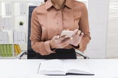 Κλείστε επάνω της γυναίκας στην καφετιά μπλούζα χρησιμοποιώντας το τηλέφωνο κυττάρων της Στοκ Φωτογραφία