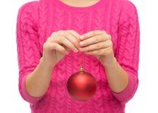 Κλείστε επάνω της γυναίκας στο πουλόβερ με τη σφαίρα Χριστουγέννων Στοκ Εικόνες