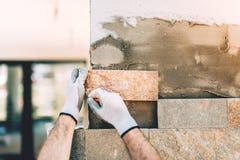 κλείστε επάνω της εργασίας οικοδόμων κατασκευής με την πέτρα και της επίστρωσης Στοκ Εικόνα