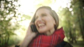 Κλείστε επάνω της εύθυμης νέας ομιλίας γυναικών στο κινητό τηλέφωνο στο όμορφο πάρκο φθινοπώρου φιλμ μικρού μήκους